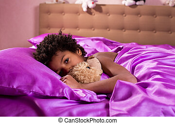 Boy in bed with teddybear.