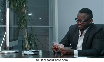 Afro businessman counting cash, sitting at desk in office