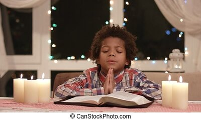 Afro child praying. Black kid prays beside window. Boy's...