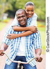afro estadounidense, pareja, en una bicicleta