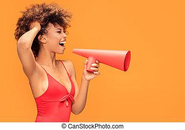 Afro girl screaming by megaphone.