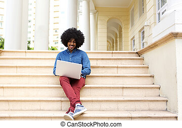 Afro man sitting on steps using laptop