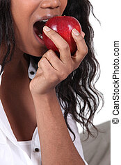 Afro woman eating apple