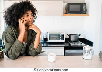 Afro woman talking on the phone at home.