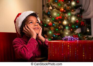 Afroamerican boy near Christmas present.