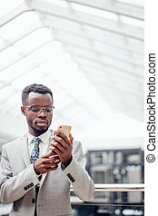 afroamerican Businessman texting on phone in mall or hall of modern office