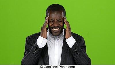 Afroamerican guy in costume experiences a severe headache. Green screen