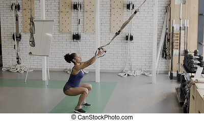 Afroamerican sportswoman is doing squats in modern gym,...