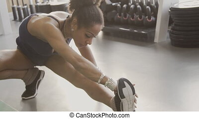 Afroamerican sportswoman is having a training in the gym....