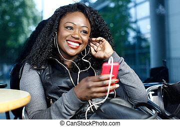afrykańska kobieta, słuchająca muzyka, outdoors