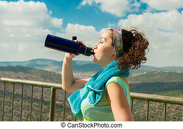 After an intense sport, a girl drinks water with pleasure