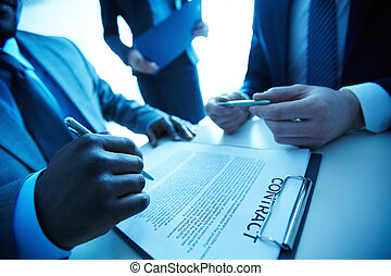 After negotiations - Image of contract on workplace and...