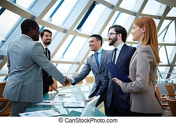 After negotiations - Two businessmen handshaking after...