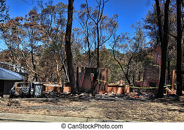 After the fire. Bushfire destroys homes and vehicles in a random pattern while some are spared completely, others are razed to the ground.