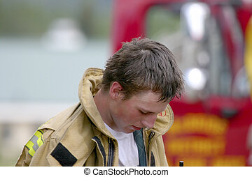 After the fire - Young fireman tired after the fire is out.