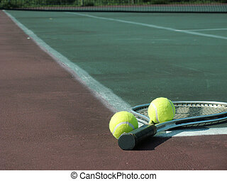 after the game - tennis racket and two balls lying on the...