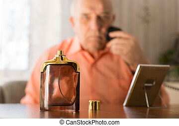 Aftershave Bottle In front Old Man Shaving Beard