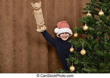 afuera, navidad, niño, píos, él, chica descocada, casero, atrás, árbol., sonrisas, cheerfully.