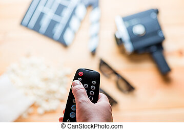 against the backdrop of the film industry objects close-up of TV remote in a female hand