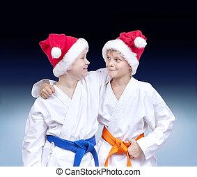 Against the background gradient athletes in caps of Santa Claus