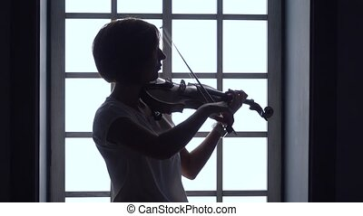 Against the background of a window girl plays the violin . Silhouette
