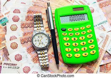 Against the background of Russian five-thousandth bills lies a calculator with the number one million, a watch and a pen
