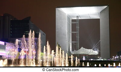 Agam fountain (Puteaux) in front of Grand arch La Defense at Paris by night
