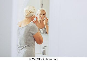 Nice aged woman looking at her reflection