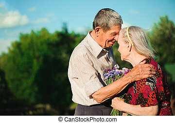 Age couple in love holding hands on a walk in the park in summer.