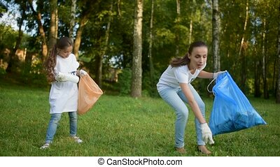 Age diverse volunteers picking up litter outdoors - From...