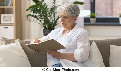 senior woman writing to notebook or diary at home - age,...