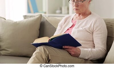 senior woman in glasses reading book at home - age, leisure...