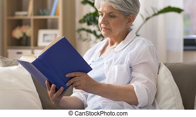 senior woman reading book at home - age, leisure and people...