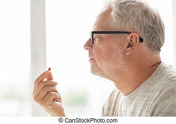 close up of senior man taking medicine pill - age, medicine,...