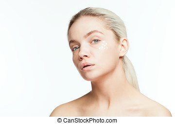 Age protection. Young woman with drops of face cream on face