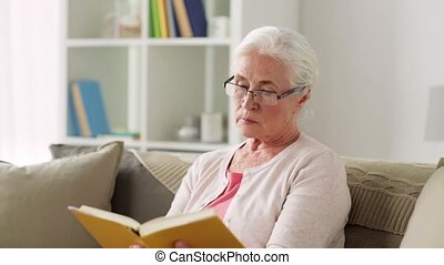 senior woman in glasses reading book at home - age, vision...