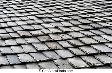 Aged black slate roof tiles background.
