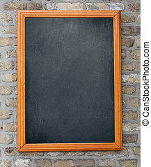 Aged blackboard hanging on brick wall as a background for your m