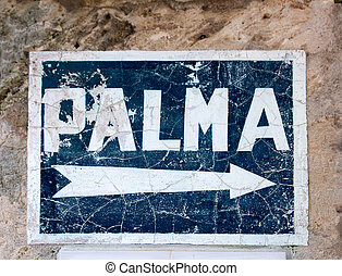 Aged blue road sign with arrow to Palma de Majorca hand...
