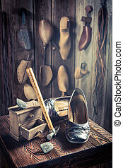 Aged cobbler workshop with tools, shoes and laces