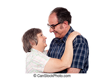 Aged couple in a romantic mood looking each other