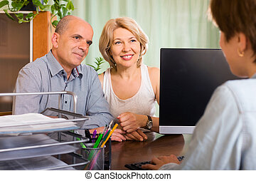 aged couple of pensioners talking with employee