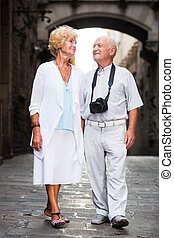Aged couple on vacation roaming - Smiling aged man and woman...