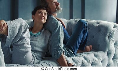 aged couple sitting on the couch