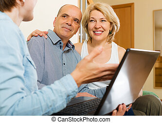 Aged couple talking with employee with laptop