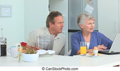 Aged couple using a laptop during the morning in the kitchen