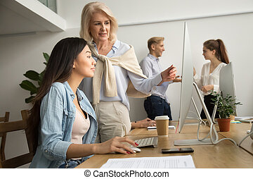 Aged female mentor helping asian girl intern explaining computer