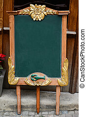 Aged green blackboard in front of restaurant entrance ready for your text