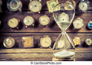 Aged hourglass on the background of clocks