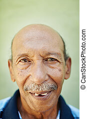 aged latino man smiling at camera - portrait of senior...